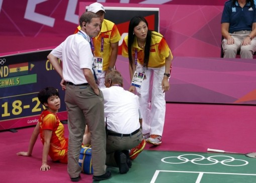 China's Wang Xin, her coaches Tang Xuehua and Zhang Ning, and official look across court after Wang sustained knee injury during her women's singles badminton bronze medal match against India's Saina Nehwal at London 2012 Olympic Games at Wembley Arena