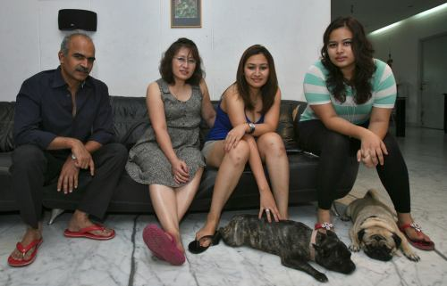 India's badminton player Gutta poses for a photograph with her family at her residence in the southern Indian city of Hyderabad